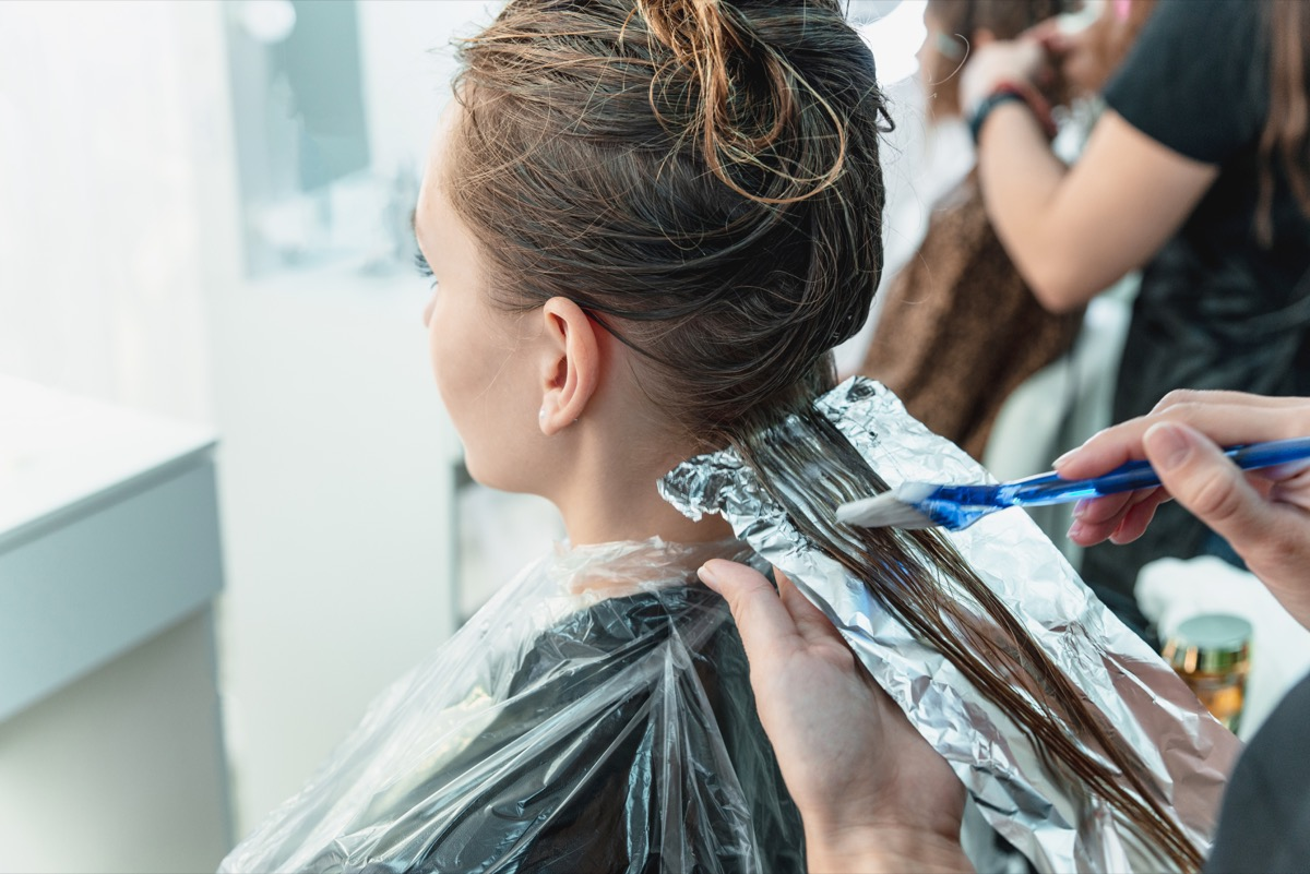 Woman getting her hair dyed with foils