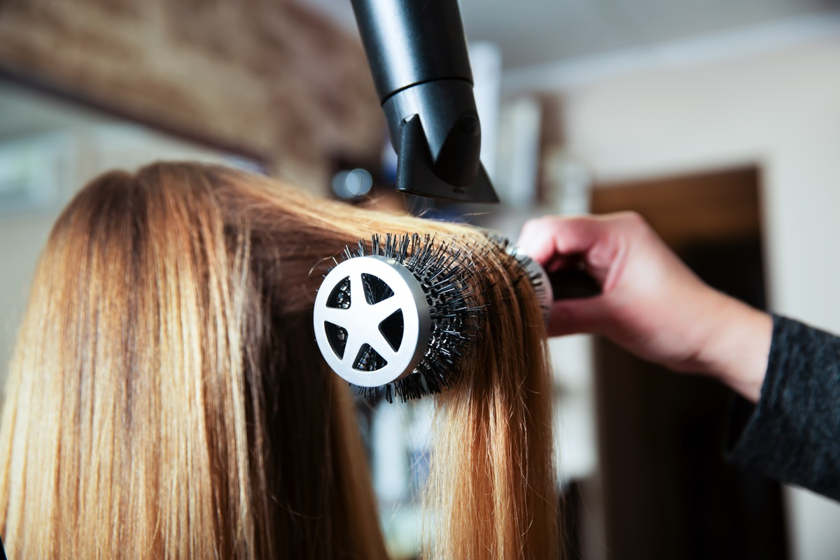 Professional woman hairdresser making hairstyle using hair dryer for young female in beauty salon.