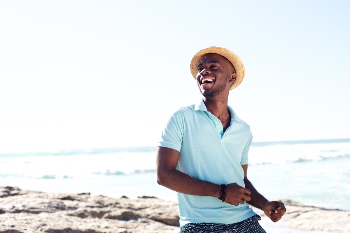 Happy man on the beach wearing a hat