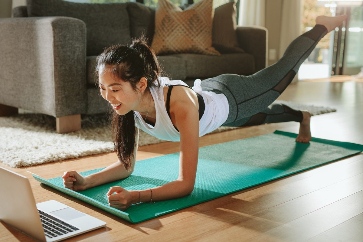 Girl doing at home workout with laptop