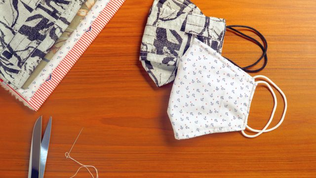 DIY homemade mask to fight coronavirus on wooden desk with fabric and scissors