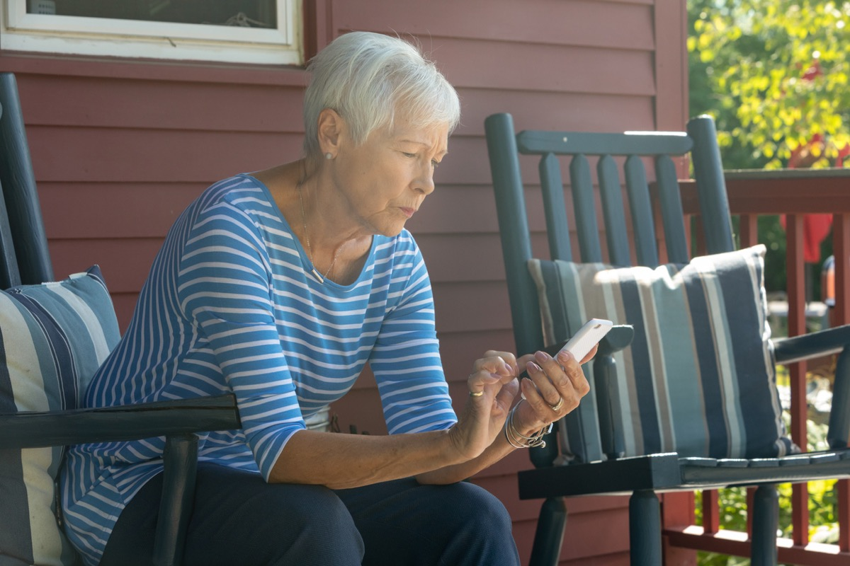 older white woman texting outside while looking concerned