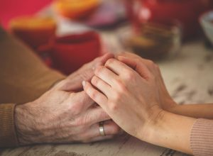 Close-up shot of a married couple holding hands across table, wife not wearing wedding ring