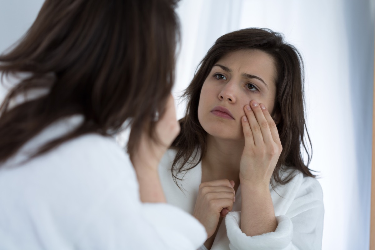 young woman looking concerned with her hand by her eye in mirror