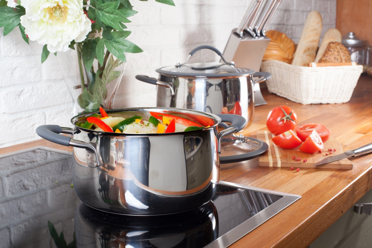 Induction cooking stove with pot of vegetables