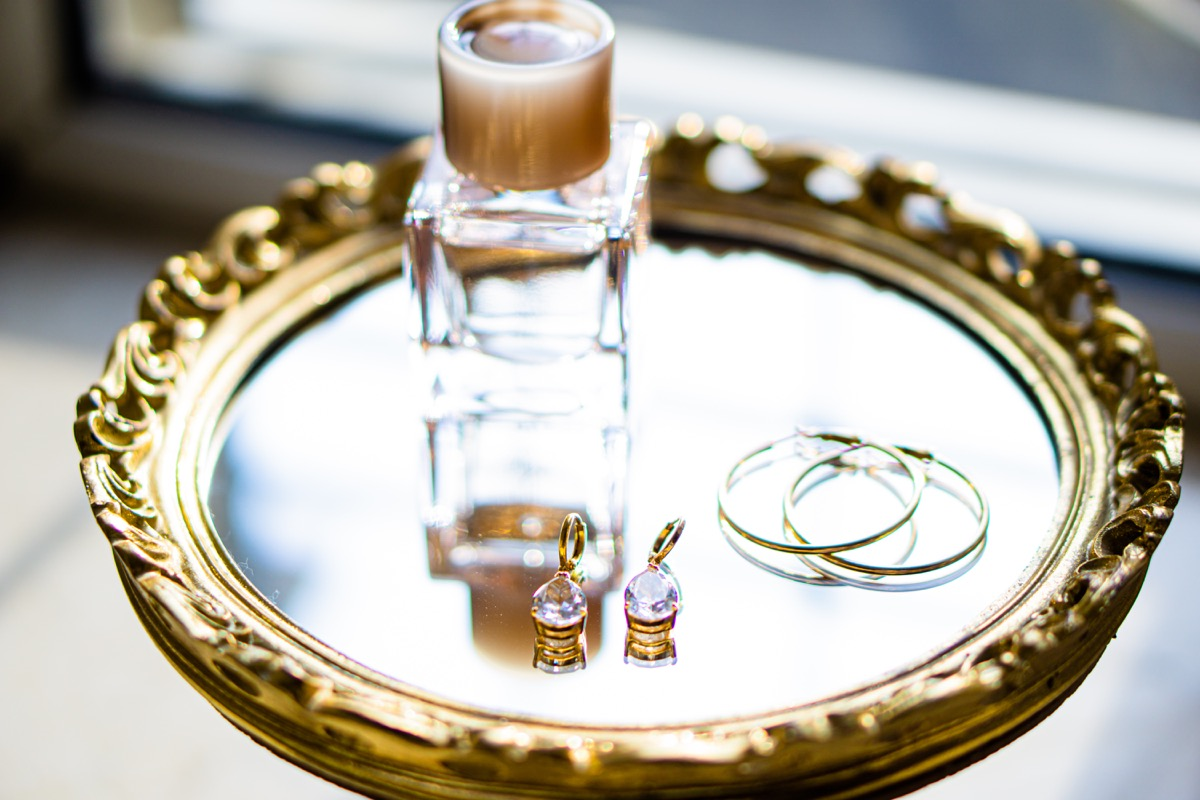 earrings and perfume bottle on gold mirrored tray
