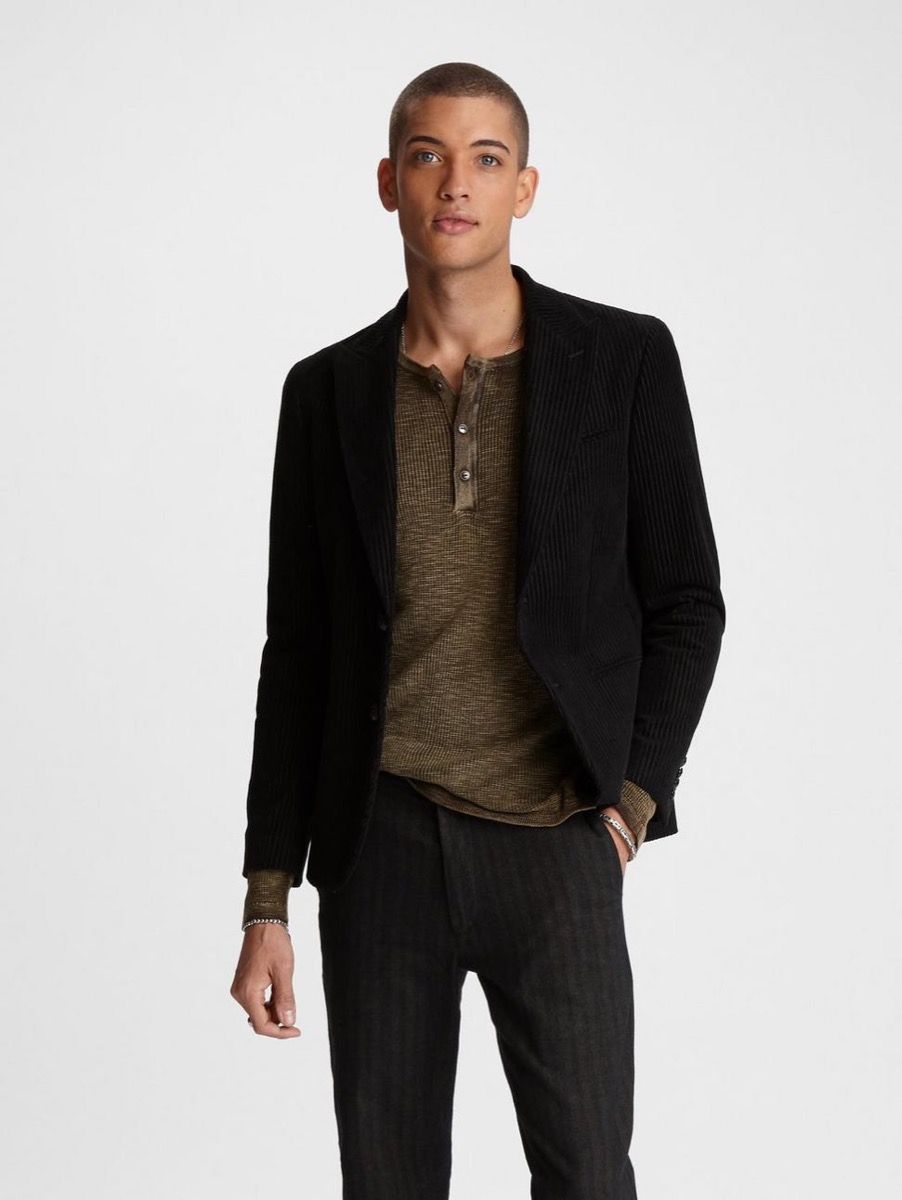 young man in brown shirt, black blazer, and black jeans