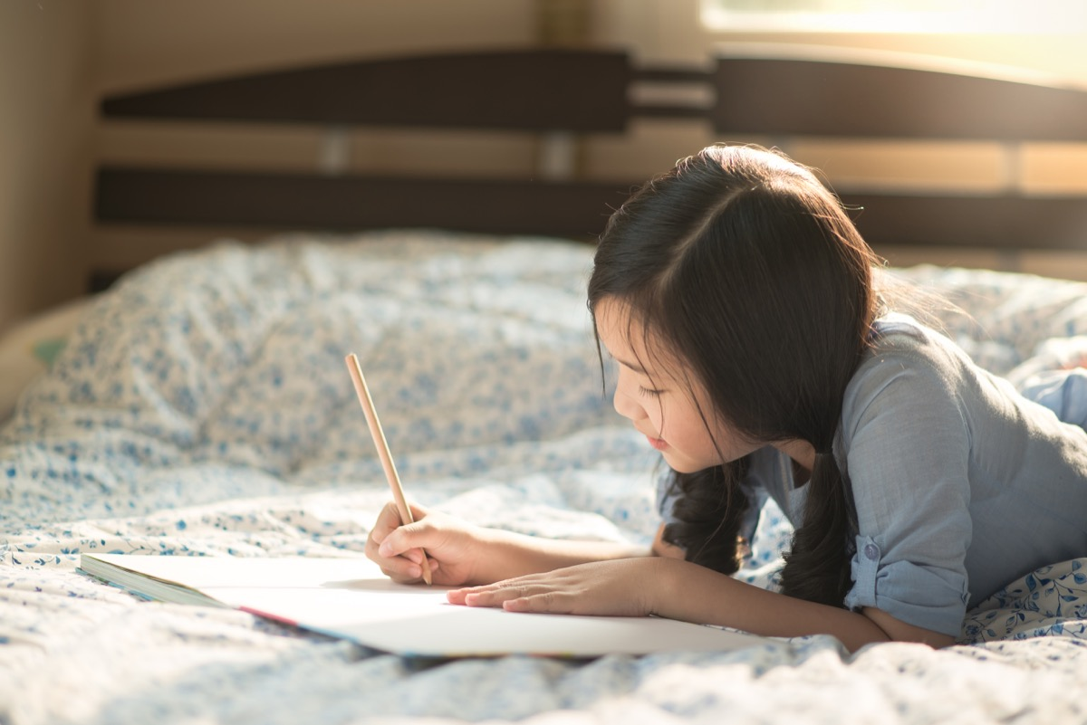 Young girl journaling on bed