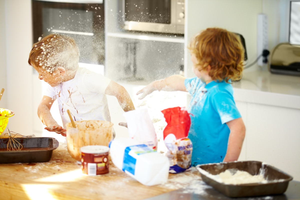 Little boys covered in baking ingredients during a messy baking session