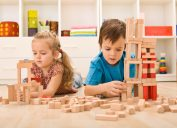 two young white kids playing with wooden blocks