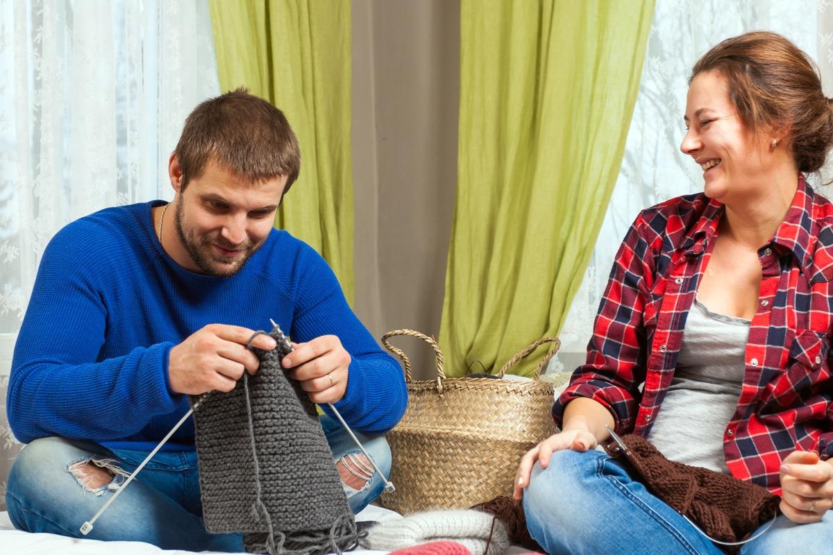 Woman teaching man to knit