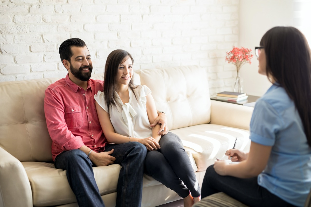latinx man and woman smiling at female couples therapist