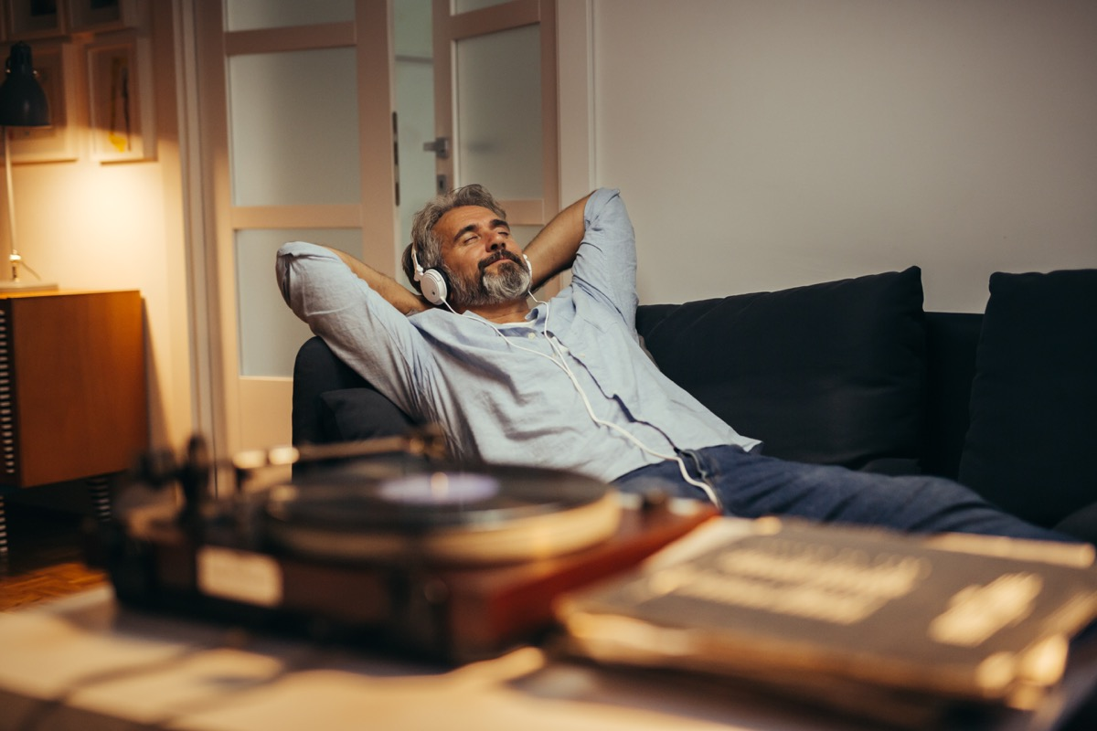 Man listening to headphones relaxing on his couch