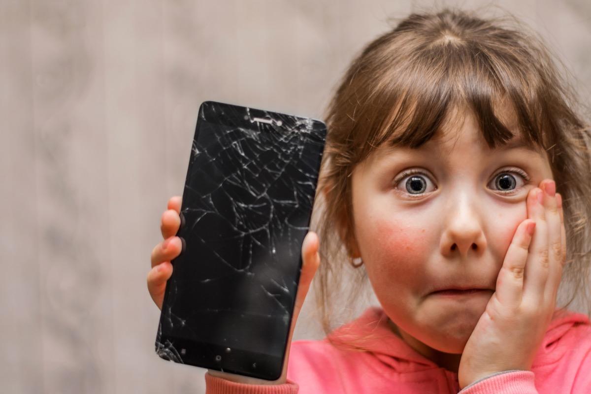 little white girl holding broken phone