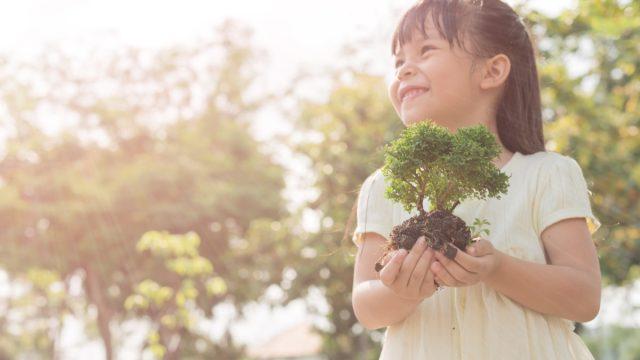 little girl holding plant oudoors
