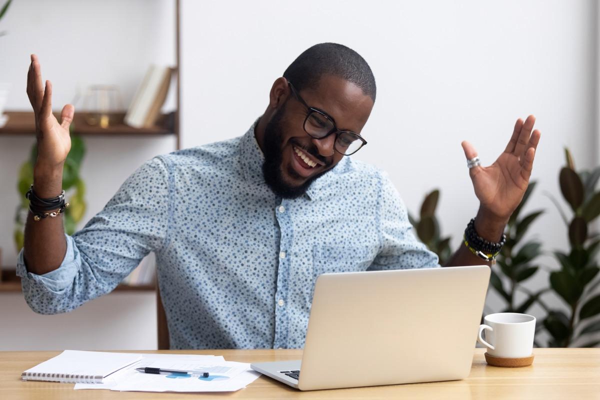 black man sitting at desk looking at computer screen talking on video call