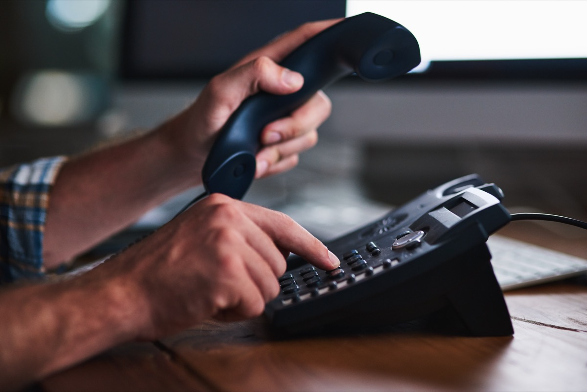 man calling and dialing on a landline phone