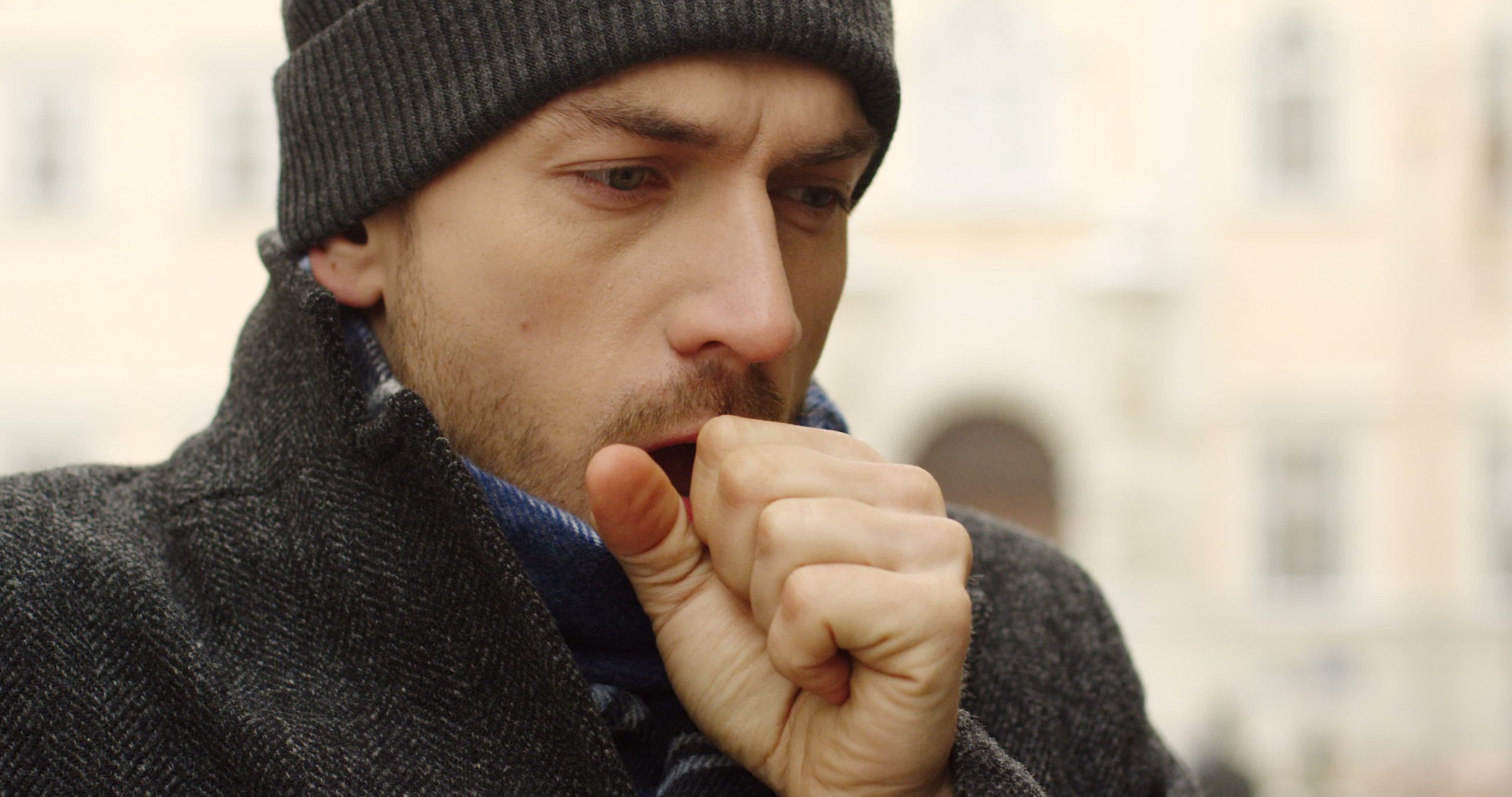 white man in coat and hat coughing into his hand