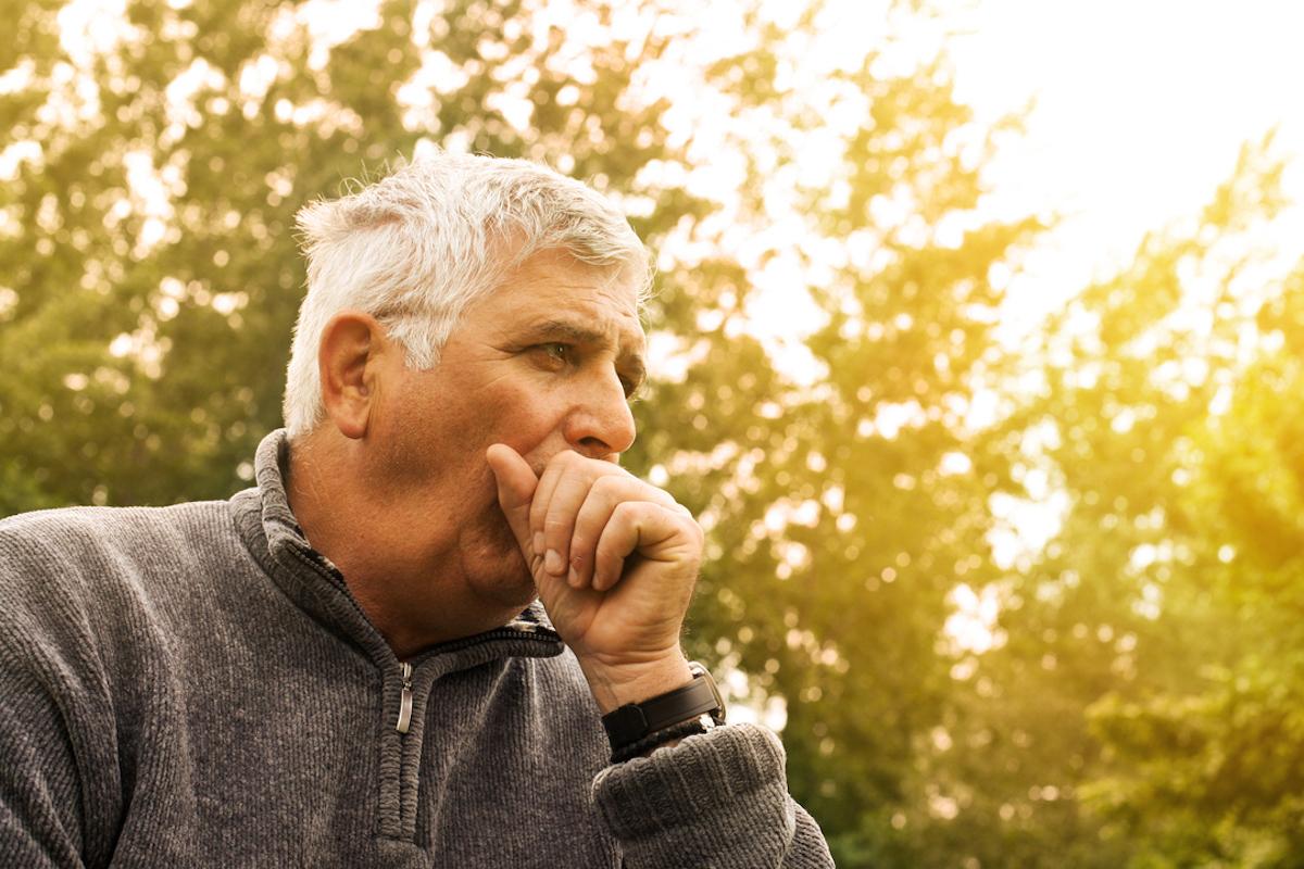 Coughing Senior Man on fresh air, considering symptoms of coronavirus