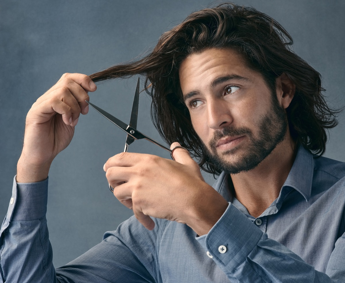 Studio shot of a handsome young man cutting his hair against a grey background