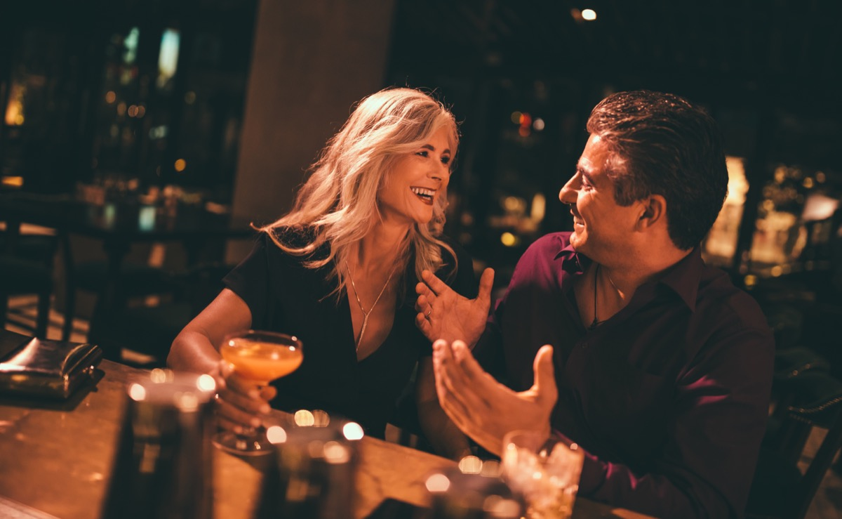 man flirting with older woman at the bar