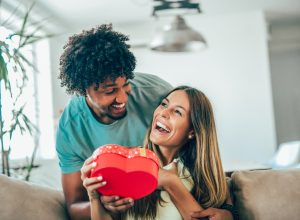 Man giving his girlfriend or wife a heart-shaped present