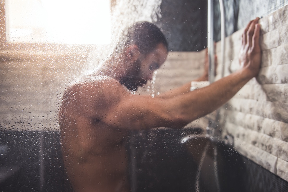 young black man leaning against shower wall with head in spray