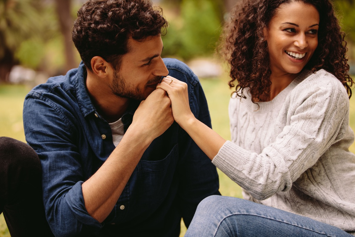 man kissing a womans hand on a park bench