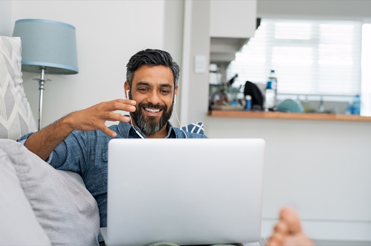 middle-aged man of color relaxing on couch while video calling using laptop at home