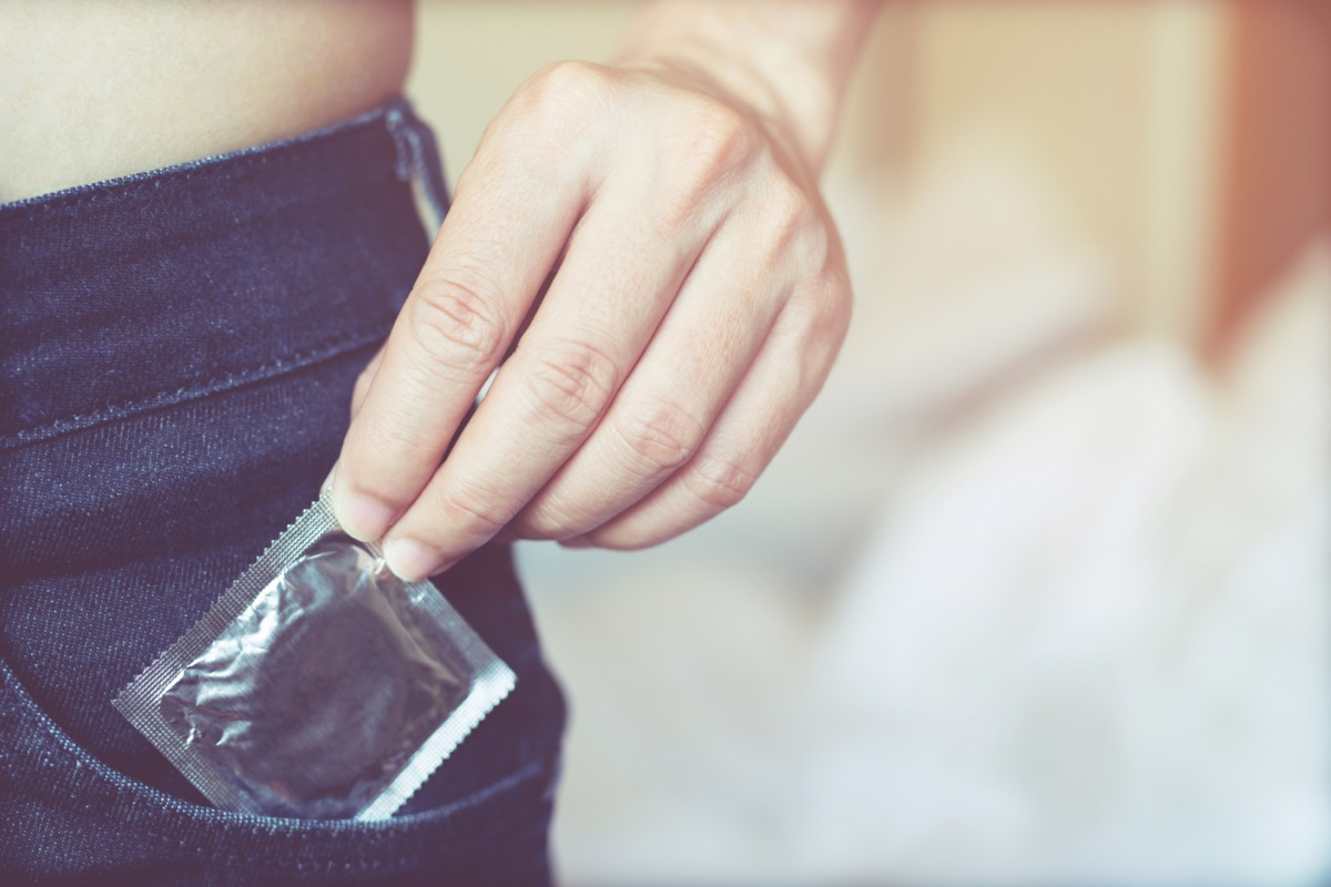 hand of a man putting a condom into his front jean pocket