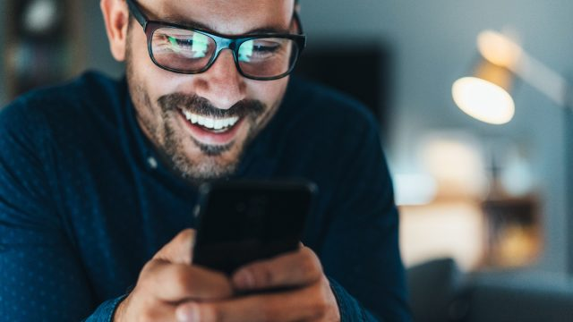 Young man wearing glasses and laughing while looking at jokes on his phone