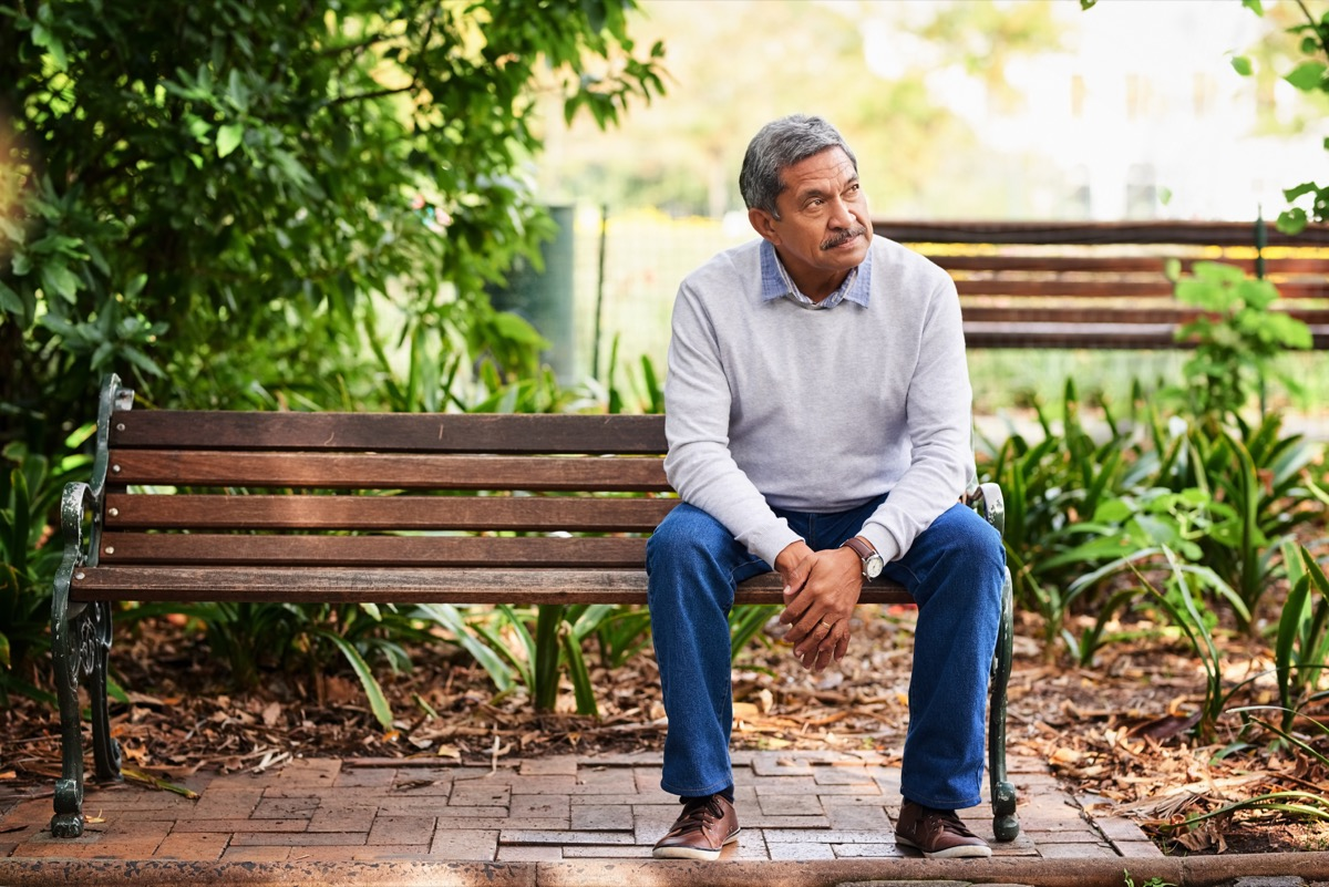skeptical man sitting outside looking off into distance