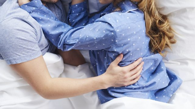 white man and woman holding each other in pajamas in bed