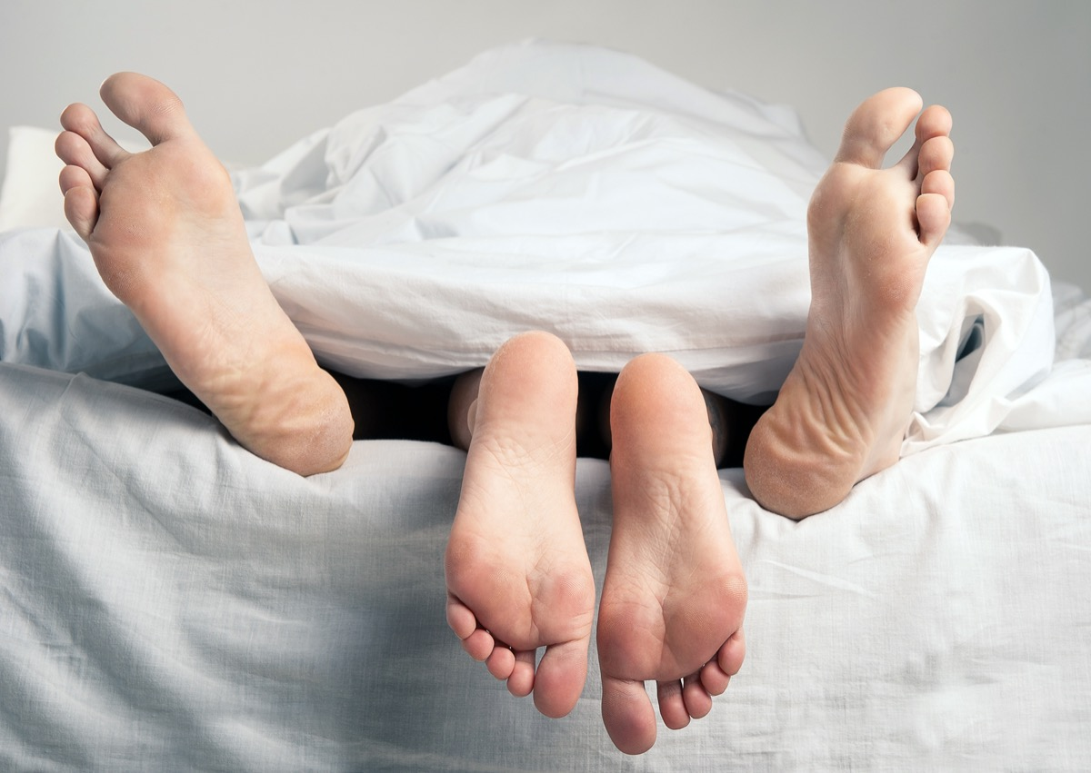 bare feet of a man and woman peeking out from underneath white sheets