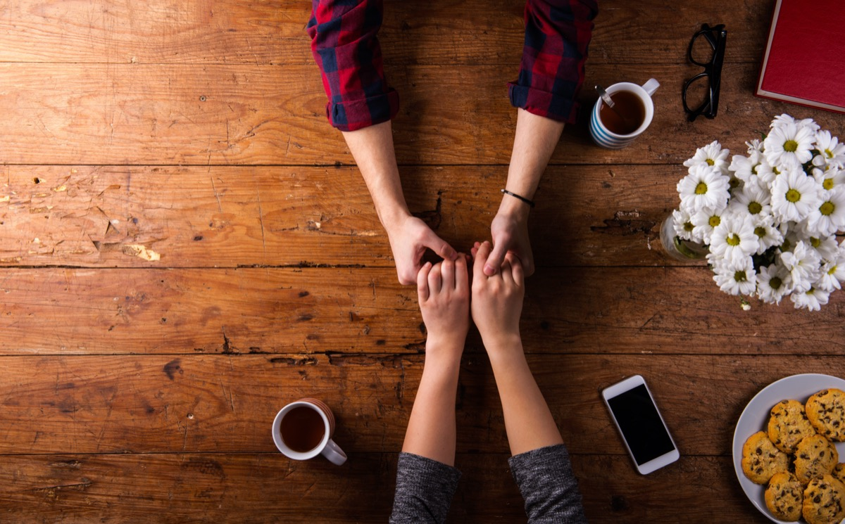 overhead shot of a man and woman holding hands on a wooden table top