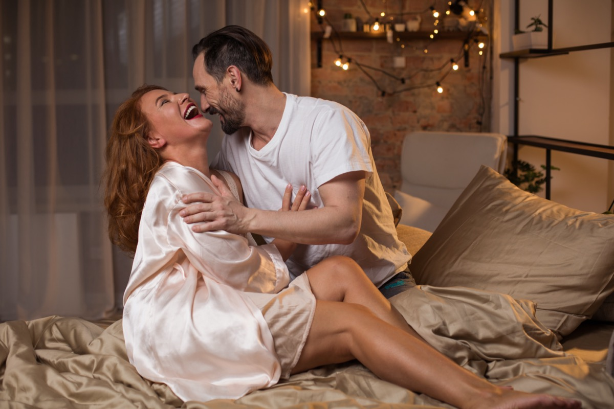 white mature woman in light pink robe and white mature man in white t-shirt laughing and hugging in bed