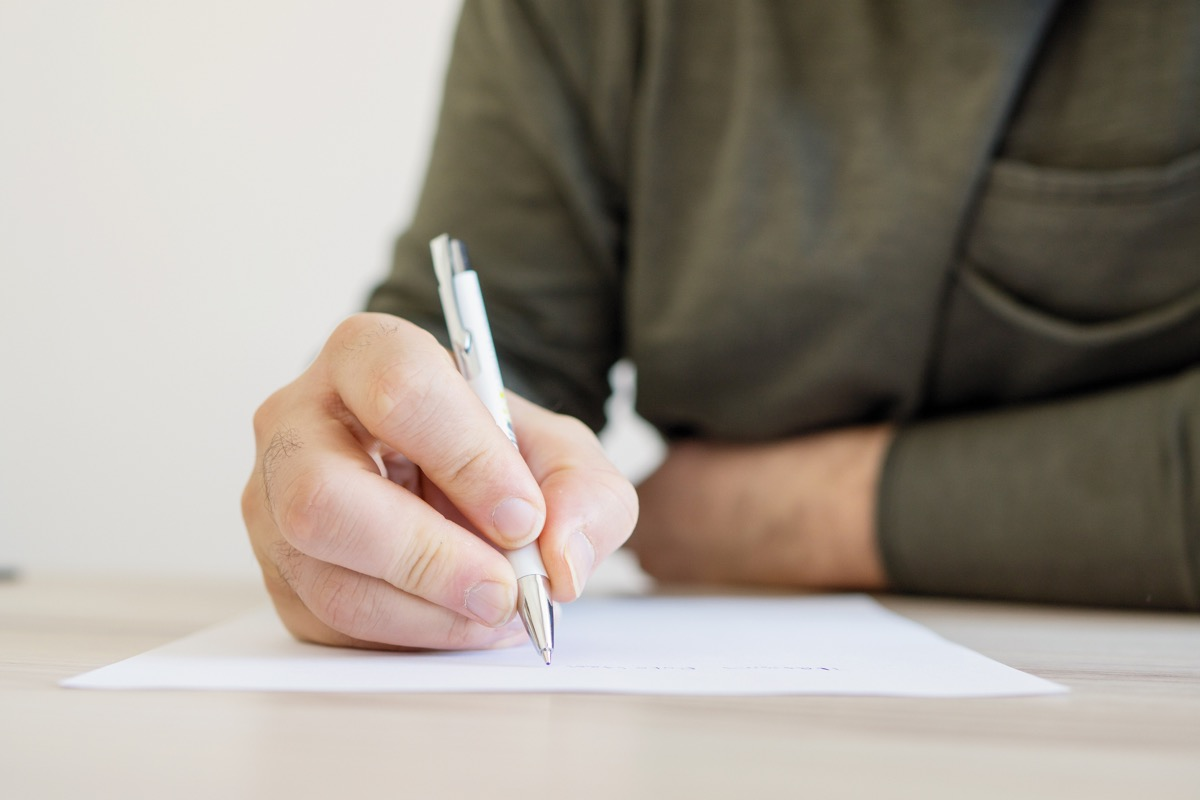 man writing a letter with a pen