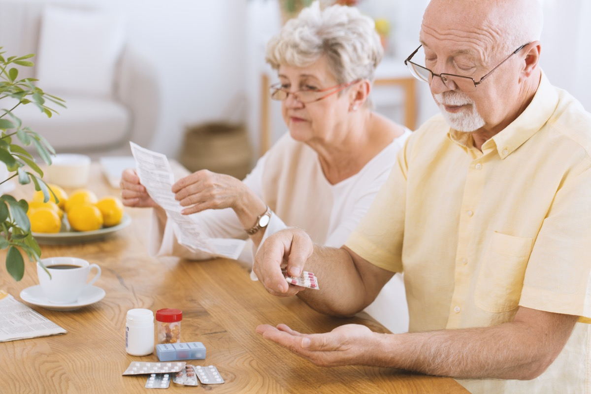 Older couple taking medications reading instructions carefully