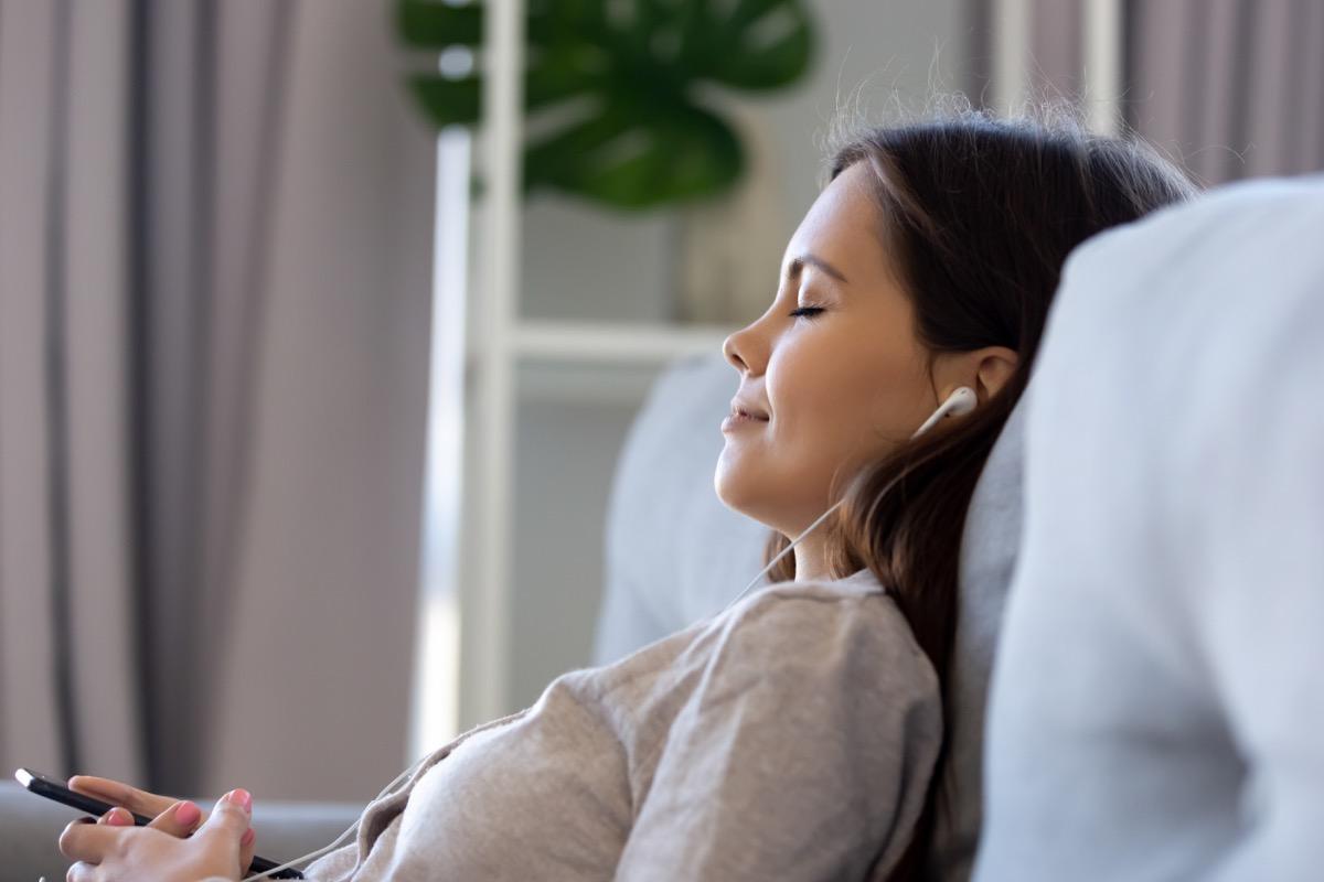 Woman meditating with earphones in
