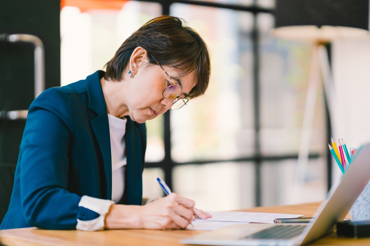 middle aged asian woman working at home at wfh office desk