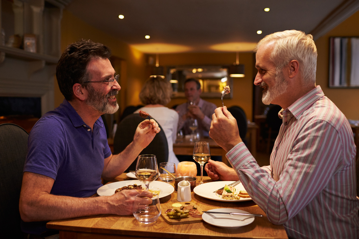 Middle aged male gay couple eating dinner in a restaurant