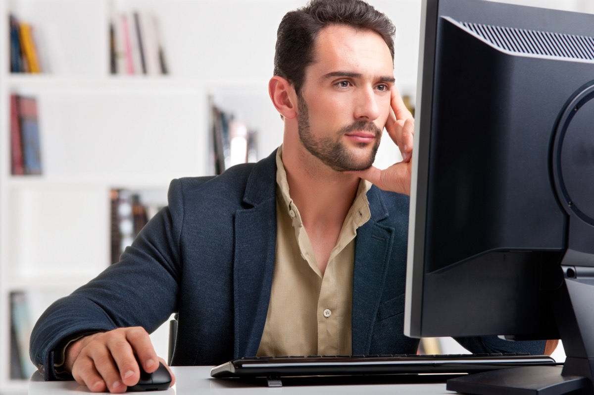 middle aged white man working at large computer monitor while working from home at wfh office