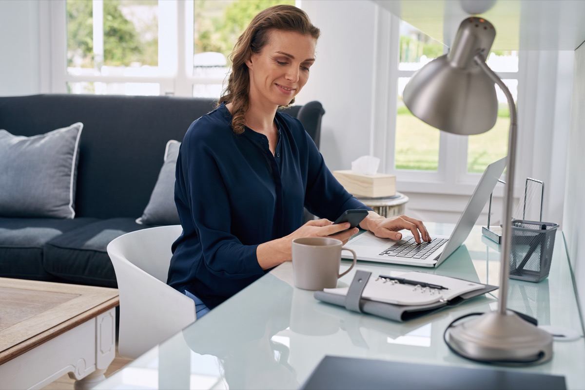 middle aged white woman working at desk in home office working from home
