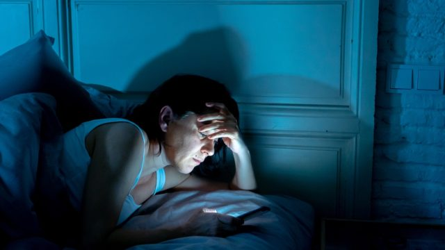 middle aged woman on her phone in bed at night