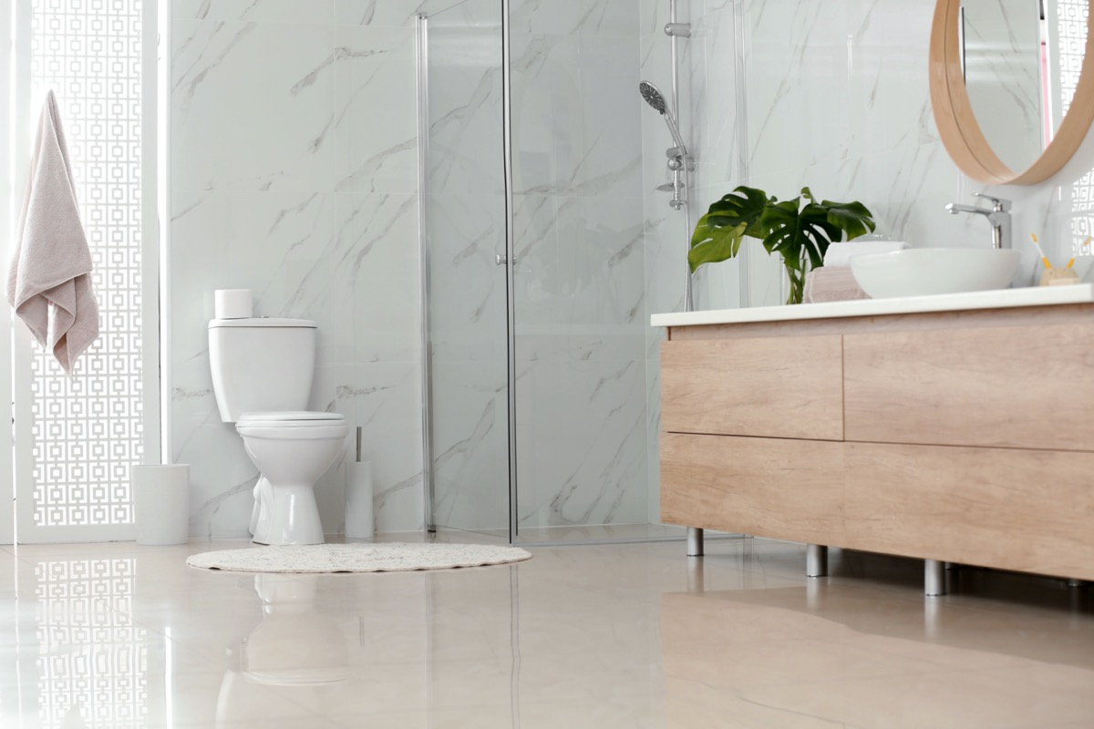 modern bathroom with marble walls white toilet and light wood furniture