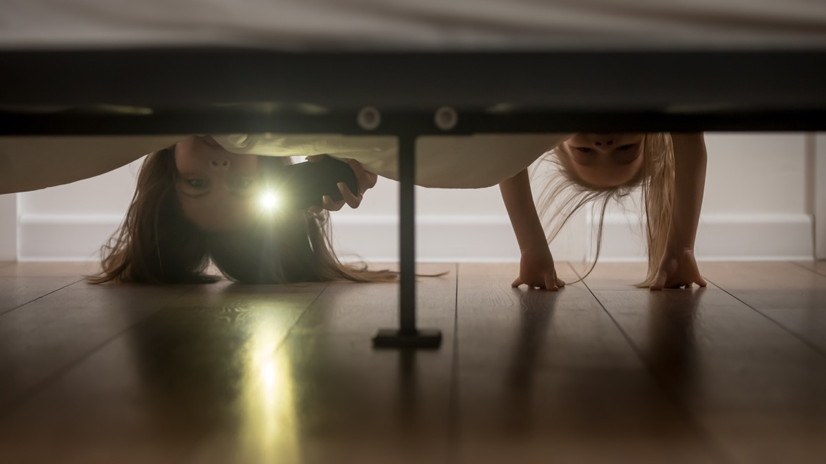 mother and daughter looking under bed with flashlight