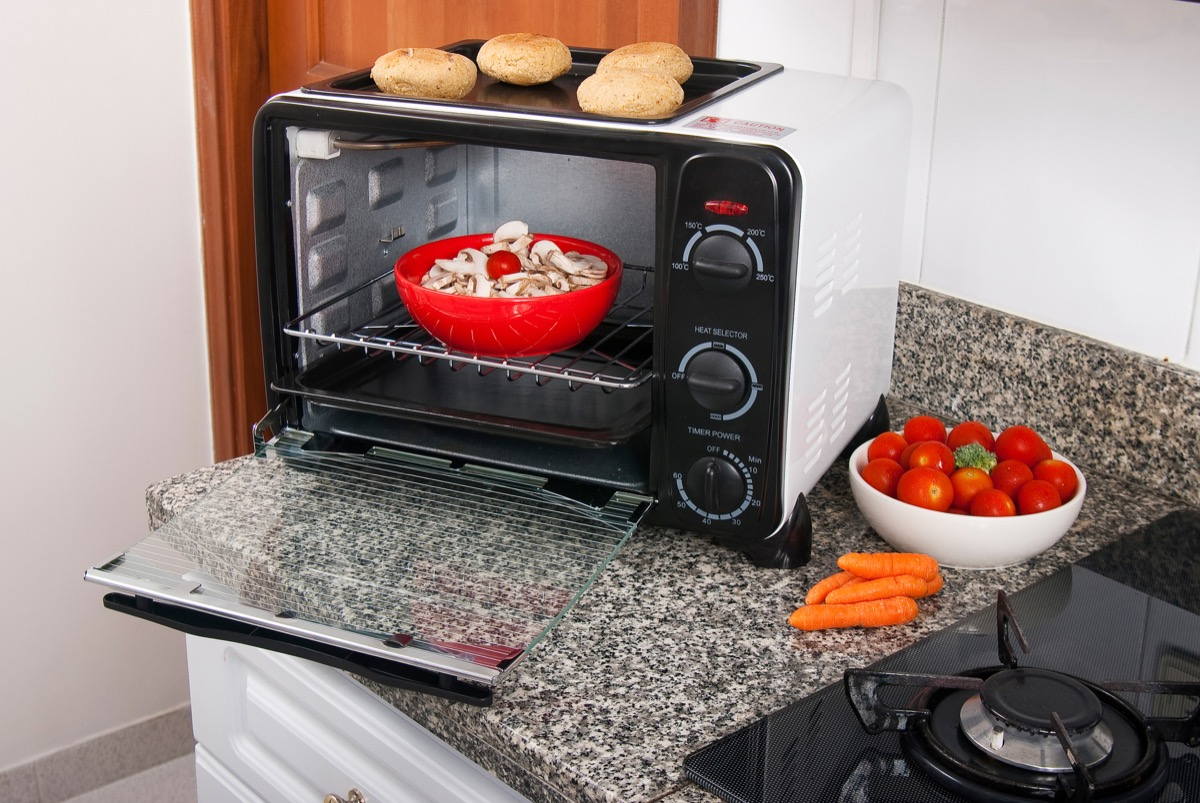 red bowl of mushrooms in toaster oven on kitchen counter