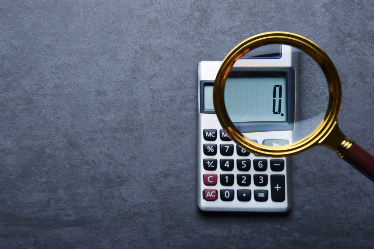 Financal concepts, a calculator showing zero with magnifying glass