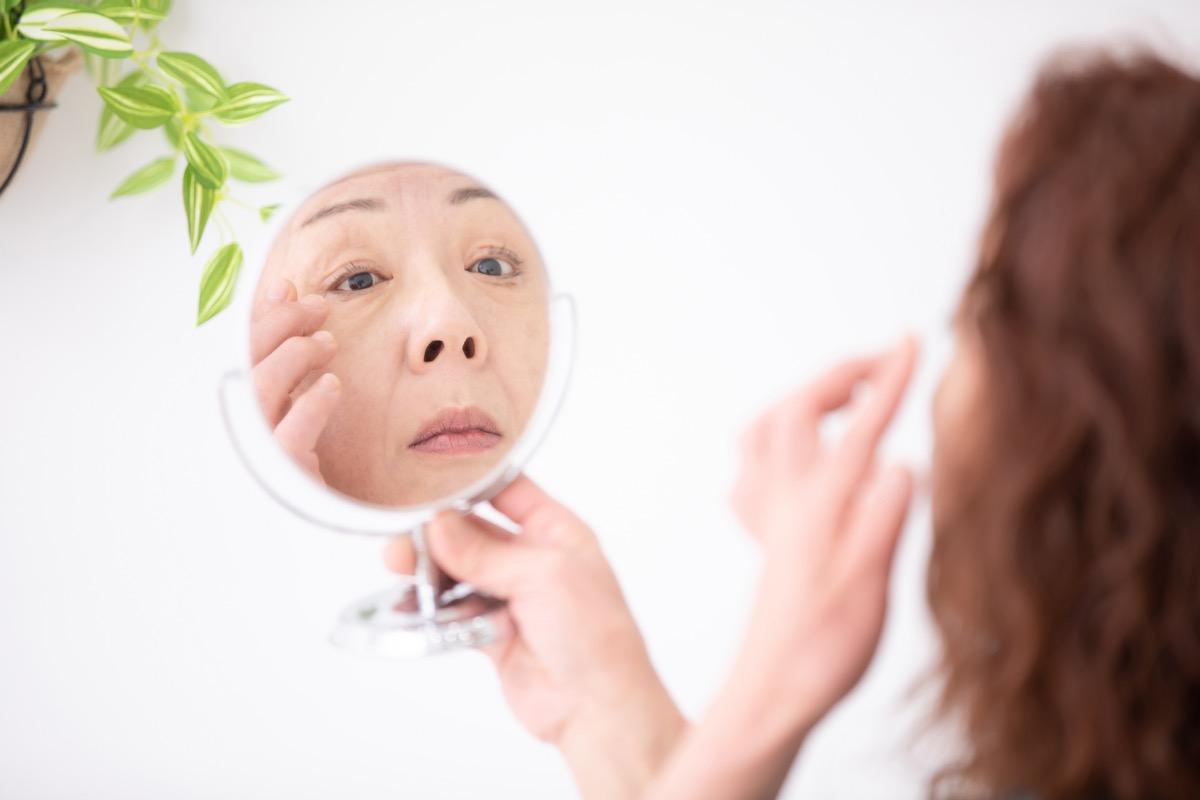 older asian woman applying eye cream
