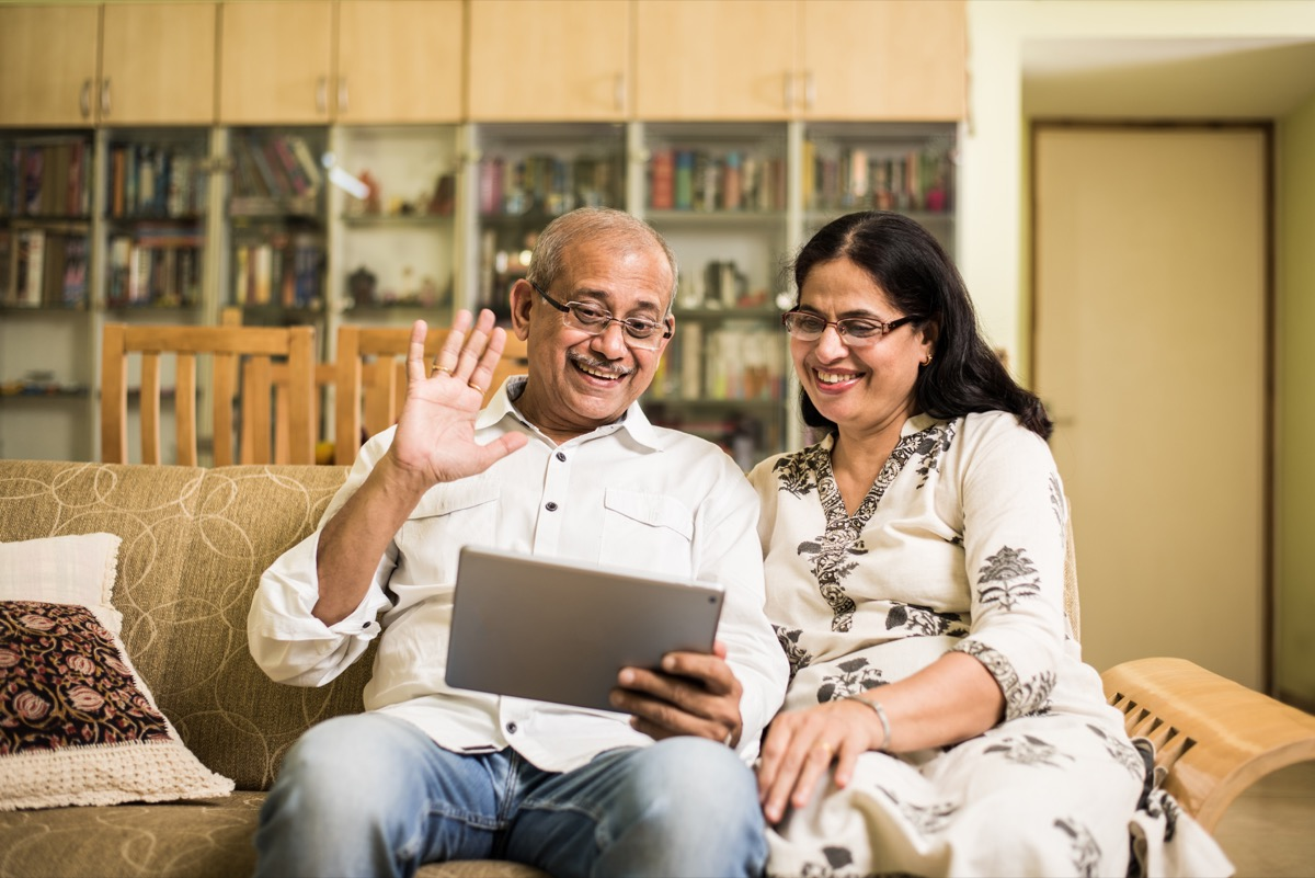 older indian couple using tablet to video chat